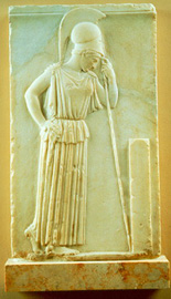 The goddess is clad in an Attic peplos with a belt and slightly bends her head towards the stele depicted in front of her